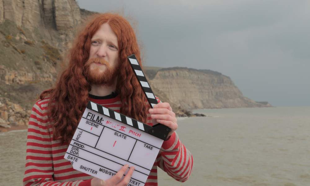 Alasdair Beckett-King holding the slate for the Nelly Cootalot: The Fowl Fleet pitch video.